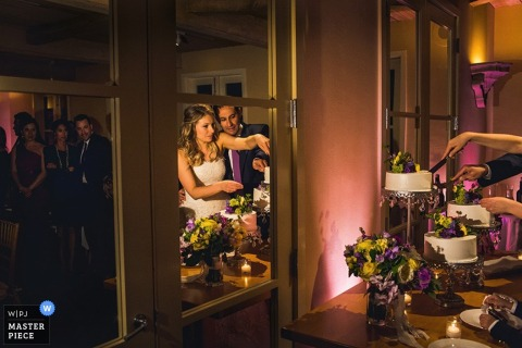 The bride and groom are reflected in a mirror as they cut their cake in this photo by a San Francisco, CA wedding photographer.