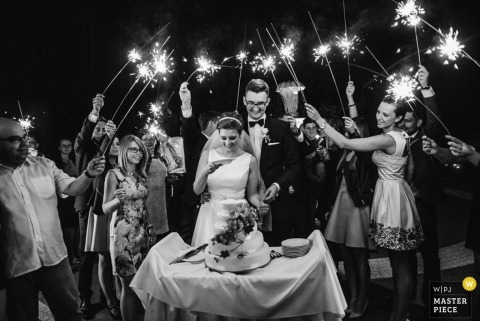 The bride and groom cut their cake as guests surround them holding sparklers in this black and white wedding image captured by an award-winning Warsaw documentary photographer.