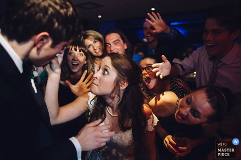 Guests watch excitedly as the bride feeds the groom a bite of cake in this wedding image crafted by a Washington, D.C. photographer.