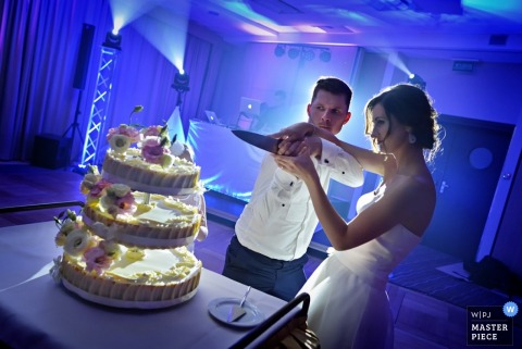 The bride and groom prepare to cut their cake together in this wedding photo composed by an award-winning Krakow photographer.