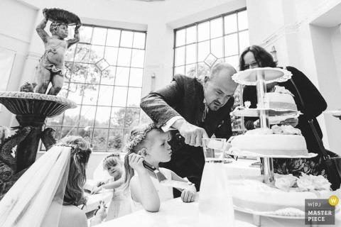 Een klein meisje staat bij de bruidstaart met een server terwijl een man het in deze zwart-witfoto snijdt, gemaakt door een bekroonde huwelijksfotograaf uit Duitsland.
