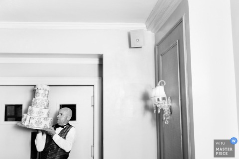 Boston wedding photographer captured this black and white photo of a caterer precariously balancing a wedding cake on one hand as he walks towards the reception
