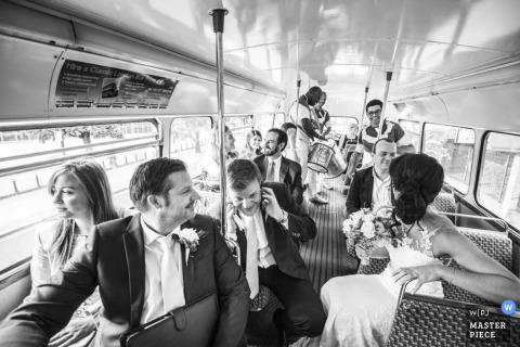 Die Brautpartei reitet auf einen Bus zusammen in diesem Schwarzweiss-Foto durch einen Hochzeitsreportagephotographen Londons, England.