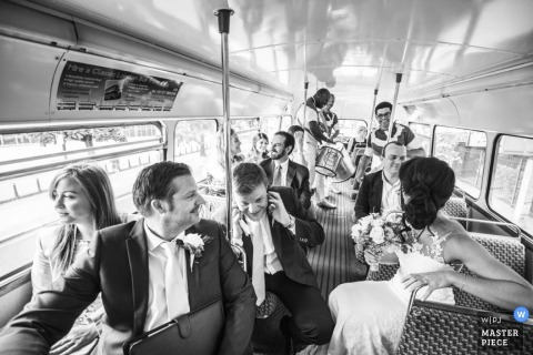 The bridal party rides on a bus together in this black and white photo by a London, England wedding reportage photographer.
