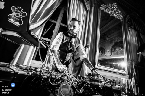 The DJ spins live music through his equipment at the reception in this black and white photo created by an award-winning Aargau, Switzerland wedding photographer.