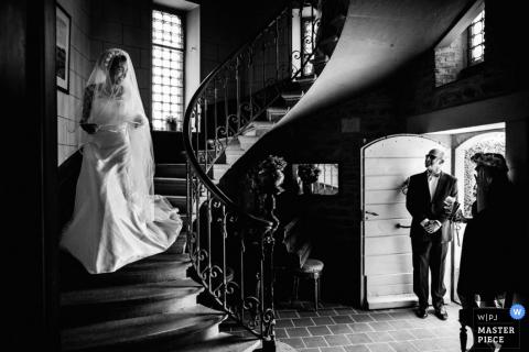 De huwelijksfotograaf van Montpellier heeft deze zwart-witfoto van de bruid gemaakt die door een wenteltrap naar beneden gaat terwijl haar ouders op de bodem wachten