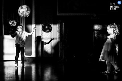 Der baden-württembergische Hochzeitsfotograf hat dieses Foto von zwei Kindern aufgenommen, die an der Rezeption mit einem Ballon spielen