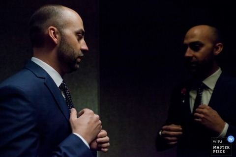 The groom gets ready in front of a mirror in this photo by a Denver, CO wedding photographer.