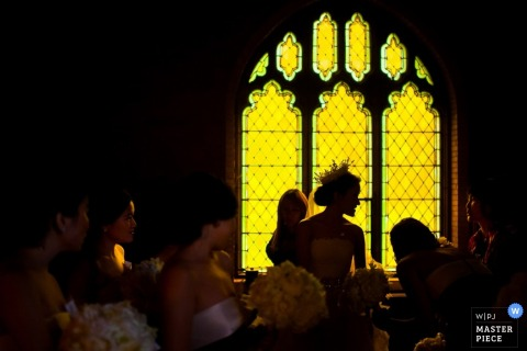 The bride is back-lit by an ornate window in this wedding picture composed by an Atlanta, GA documentary photographer.