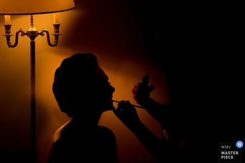 Het silhouet van de bruid is te zien terwijl ze haar make-up laat doen in deze bekroonde trouwfoto van een Siciliaanse fotograaf.