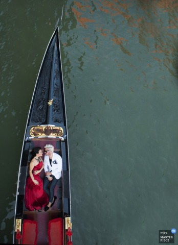 Texas wedding photographer captured this aerial photo of a bride in a beautiful red dress and a groom in a white tuxedo floating down the river on a black row boat