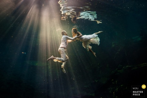 Cartago wedding photographer captured this underwater portrait of the bride and groom as they swim in streaks of sunlight