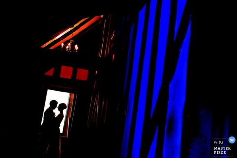 Bristol bride and groom silhouetted while hugging in a doorway - England wedding portrait