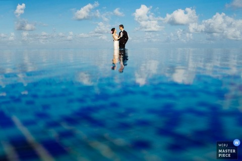 Bali bride and groom reflected in the water - Indonesia wedding portraits