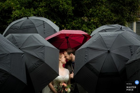 Knoxville bride and groom kiss under a red umbrella - Tennessee wedding portraits