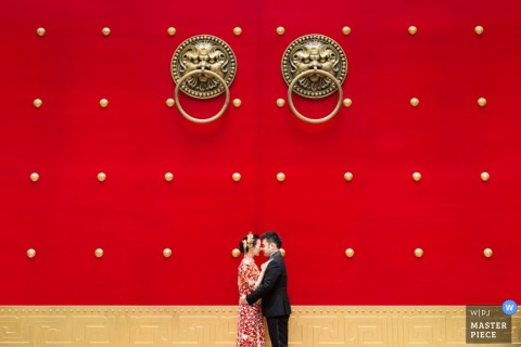 Shaanxi bride and groom hug in front of a red wall - China wedding photography