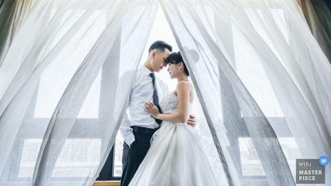 Taipei bride and groom hug in front of a window - Taiwan wedding photo
