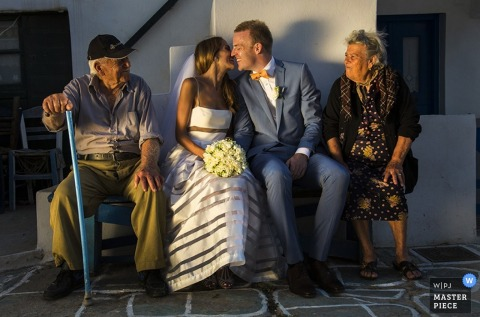 Santorini bride and groom kiss in between old couple - South Aegean wedding photojournalism