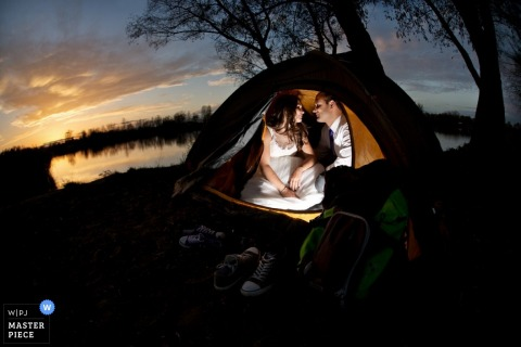Krakow bride and groom sit in a tent - Malopolskie wedding photojournalism
