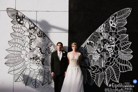 Manhattan bride and groom pose in front of butterfly wings - New York wedding portrait photography