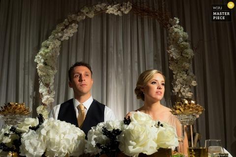 De bruid en bruidegom van Chicago zitten naast elkaar bij de lijst van het ontvangstpaar - Illinois photojournalism huwelijk
