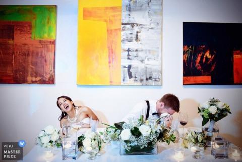 Les mariés montréalais se moquent à la table d'honneur lors des discours de réception - photojournalisme de mariage à Québec