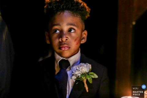 Fotograf ślubny New Rochelle uchwycił wątpliwe spojrzenie na twarz młodego nosiciela pierścienia, gdy na jego policzku widać świeżą szminkę szminki