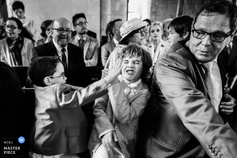 Île-de-France wedding photographer captured this black and white image of kids pestering eachother while waiting for the ceremony to start