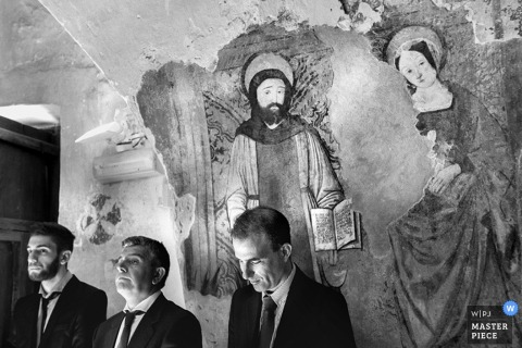 Rome groomsmen stand in front of painting - Lazio wedding photojournalism