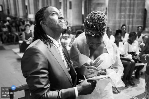 Un photographe de mariage de Seine-et-Marne a capturé ce portrait en noir et blanc d'un homme et d'une femme qui échangent des bagues alors que le marié lève les yeux en remerciement
