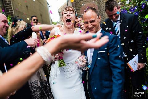 Braut und Bräutigam werden nach ihrer Hochzeit von einem Hochzeitsfotografen aus Devon, England, mit Konfetti überschüttet.