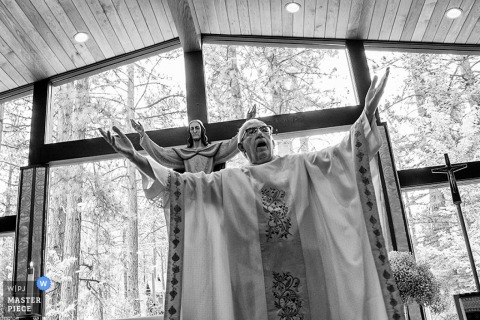 A priest officiates a wedding arms raised in front of a statue of Jesus Christ. Awarded image by a Lake Tahoe, California wedding photographer.