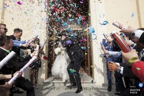 Los invitados de Varese explotan confeti hacia los novios después de la ceremonia - fotoperiodismo de bodas en Lombardía