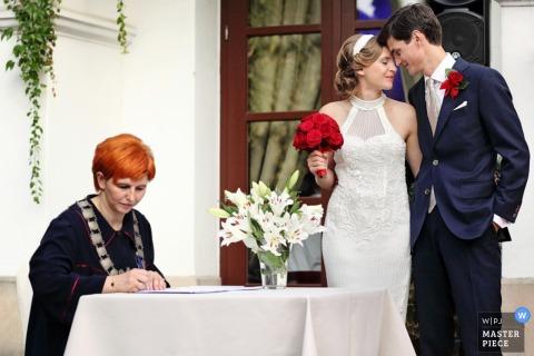 Mielec oblubienica i pan młody przytulają się na weselu, gdy podpisywany jest akt ślubu - podkarpackie zdjęcie ślubne