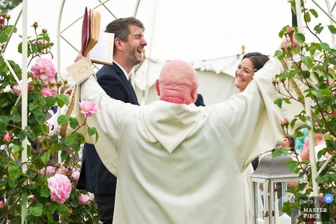 Devon bride and groom laugh with priest at the ceremony - England wedding reportage photo