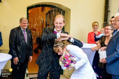 Des invités munichois jettent du riz alors que le marié couvre la mariée - Photographie de mariage Bavière