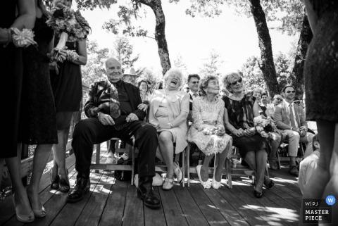 Les invités de San Fransisco rient pendant la cérémonie en plein air sous les arbres - Photographie de mariage noir et blanc