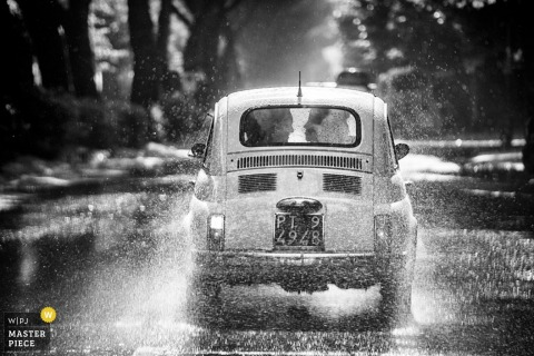 The bride and groom drive their car away in the rain in this black and white photograph by a Milan, Lombardy photographer.