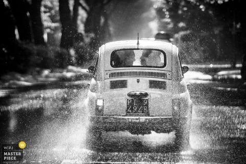 Panna młoda i pan młody odjeżdżają samochodem w deszczu na czarno-białej fotografii autorstwa fotografa z Mediolanu z Lombardii.