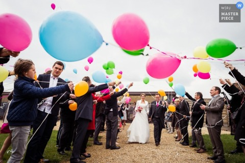 France guests fly balloons towards the bride and groom after the ceremony - France wedding photography