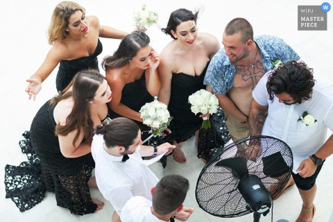 Phuket bridal party trying to cool down in front of a fan - Thailand wedding photojournalism
