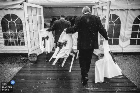 Paris groomsmen moving chairs inside in the rain - France wedding photojournalism