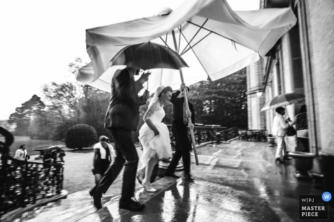 Paris man holds a huge umbrella for the bride outside in the rain - France wedding photo