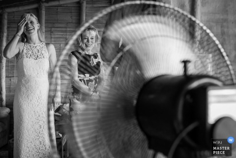 Lima bride trying to cool off on a hot day with a fan before the wedding - Peru wedding photography