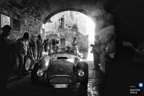 Florence bride and groom leave the wedding in an old convertible car - Tuscany wedding photo in black-and-white
