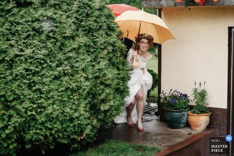 Warsaw bride running to avoid the rain in her dress - Masovian wedding photojournalism