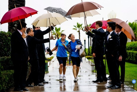 Charleston groomsmen hold umbrellas for the guests at the wedding - South Carolina wedding photo