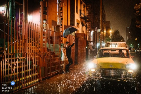 Manhattan bride and groom wait in the rain for a taxi - New York wedding photojournalism