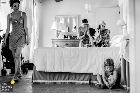 A mother searches for her daugher who is putting on her shoes. Photo by a Sciena, Tuscany wedding photographer.