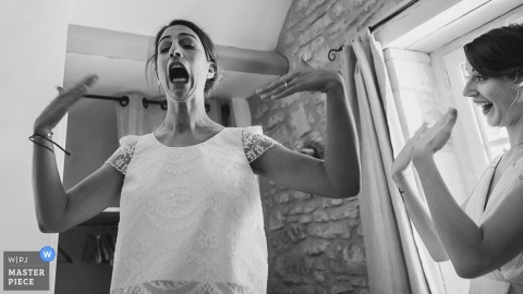 Nouvelle-Aquitaine captured this black and white photo of the excited bride rejoicing after putting on her wedding dress